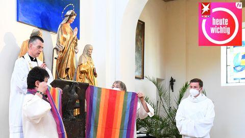 Während ein Priester in weißem Talar in einer Kirche betet, halten zwei Frauen Schals in Regenbogenfarben hoch