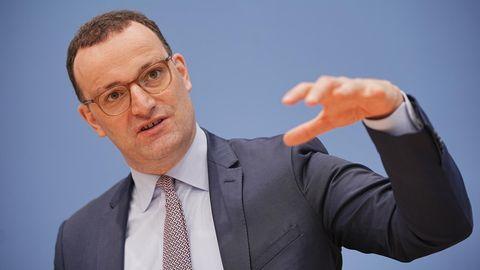 Jens Spahn spricht bei der wöchentlichen Pressekonferenz in Berlin und hebt die Hand