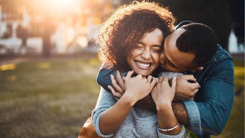 Ein glückliches Paar. Er umarmt sie von hinten und drückt ihr einen Kuss auf die Wange. Sie lächelt.