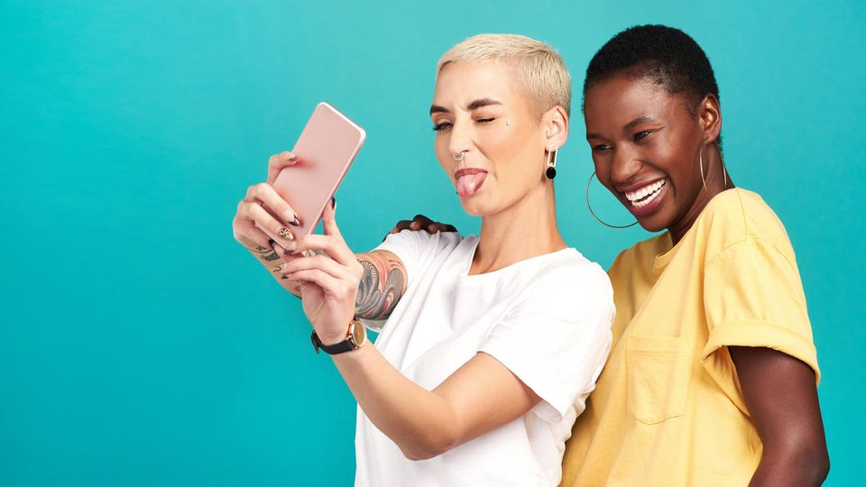 Preis Leistung Smartphone: Zwei Frauen machen ein Selfie. Die vordere streckt