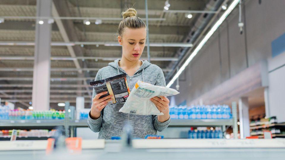 Eine Frau liest im Supermarkt die Zutatenlisten von Tiefkühlprodukten.