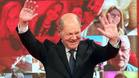 Kanzlerkandidat Olaf Scholz hebt die Hände und lächelt auf dem SPD-Bundesparteitag