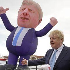 Boris Johnson und Jill Mortimer stehen neben einer über 9 Meter großen aufblasbaren Figur des Premiers
