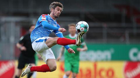 Finn Bartels von Holstein Kiel kontrolliert in der Luft den Ball