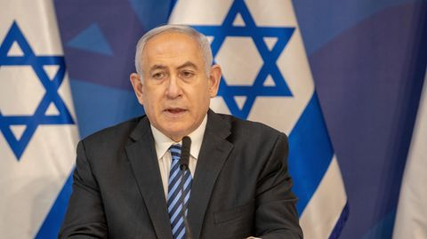 Benjamin Netanjahu sitzt vor Israel-Fahnen