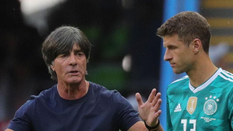 Ein schwarzhaariger weißer Mann im dunkelblauen T-Shirt erklärt einem Fußballer im hell-dunkelgrün gemusterten Trikot etwas