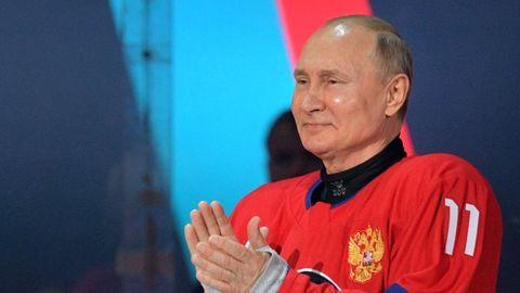 Wladimir Putin steht im Eishockey-Trikot in den russischen Farben auf dem Eis und applaudiert
