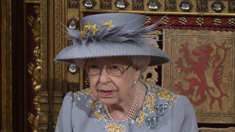 In hellblauem Kostüm mit passendem Hut sitzt Queen Elizabeth II auf einem reich verzierten Holzstuhl im britischen Parlament