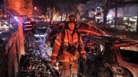 Feuerwehrmann geht durch Zerstörungen durch einen Raketneinschlag nahe Tel Aviv