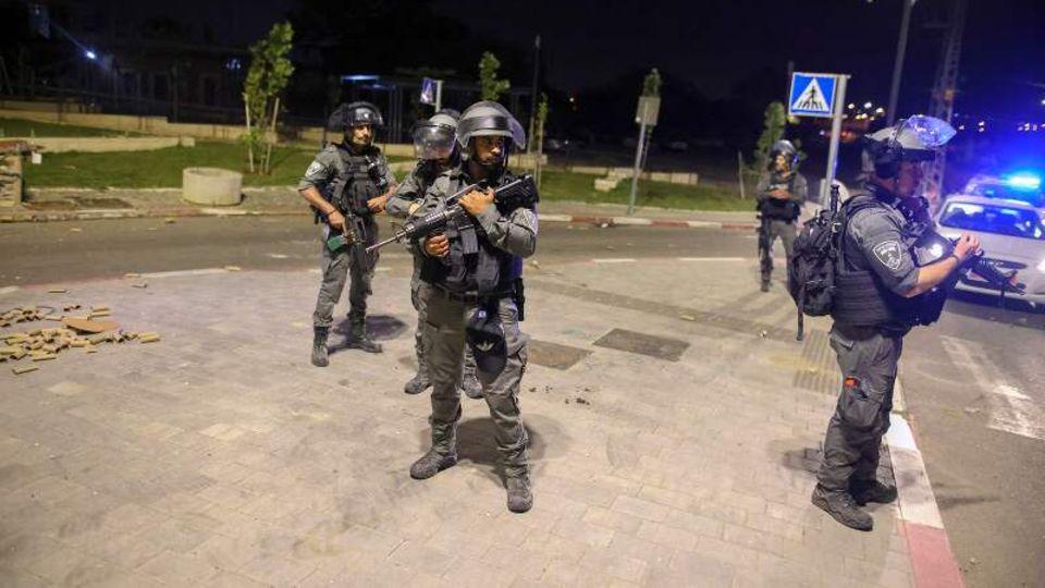 Bewaffnete und uniformierte Sicherheitskräfte stehen auf dem Bürgersteig in der israelischen Stadt Lod