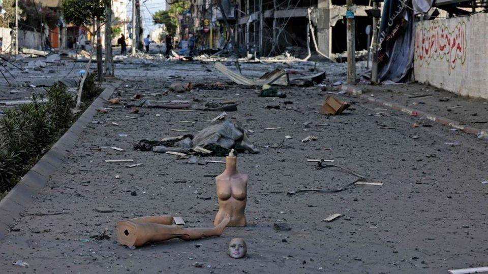 Eine Schaufensterpuppe liegt in ihren Einzelteilen auf einem Bürgersteig voller Schutt in einer von Raketen getroffenen Straße
