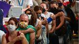 Menschen sitzen mit nackten Oberarmen in einer Reihe, weil sie sich impfen lassen wollen