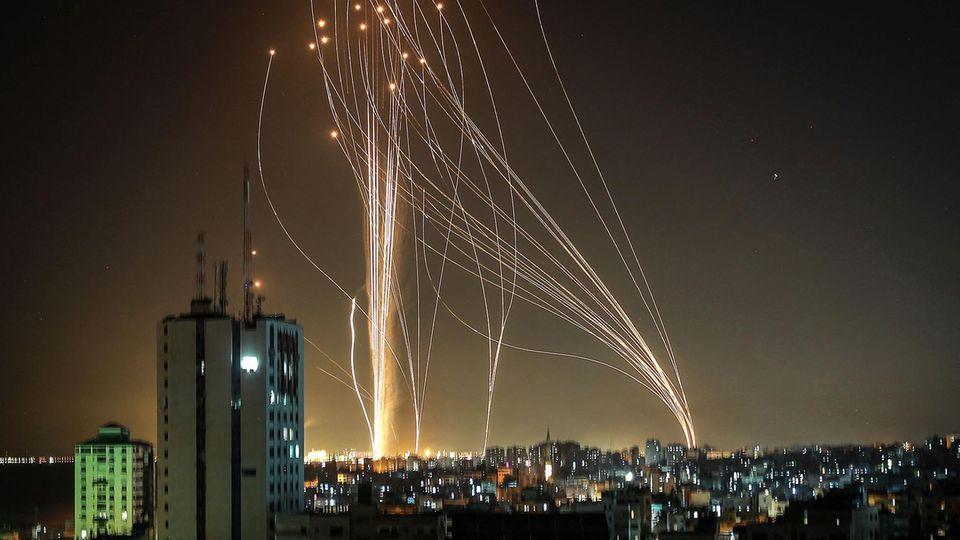 Light trails from rockets launching from two locations on the horizon run through the night sky over a city