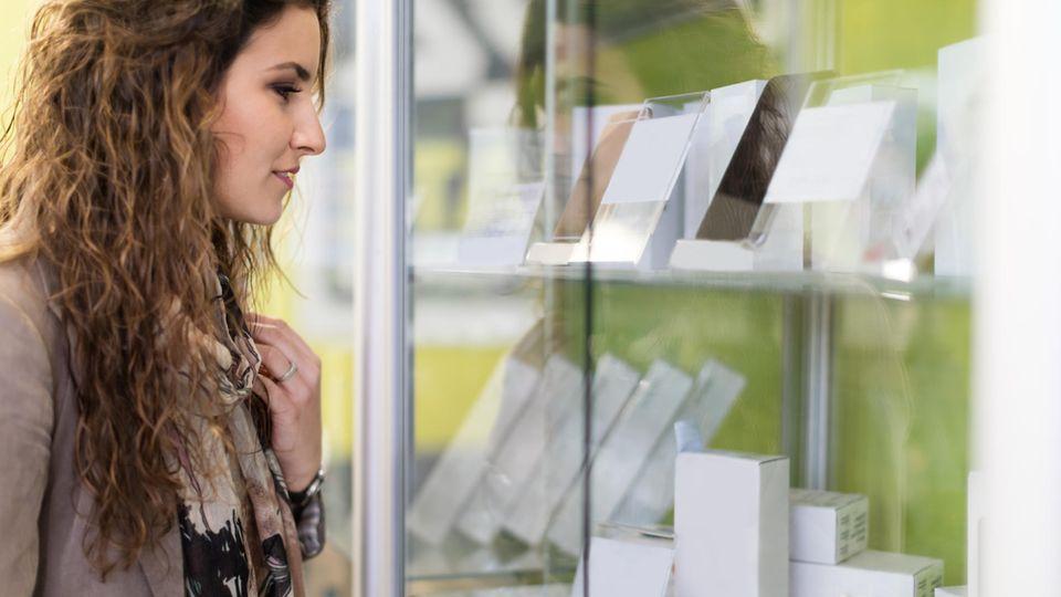 Neue Handys 2021: Eine Frau schaut sich neue Smartphones im Schaufenster an.
