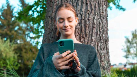 Junge Frau mit ihrem Handy in der Hand