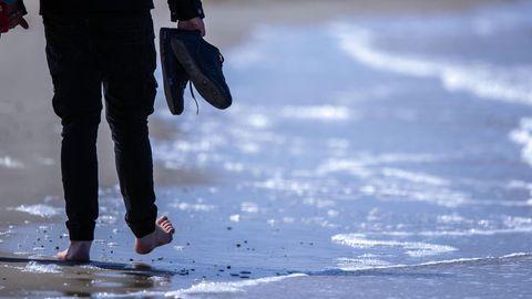 Von hinten sind die Beine eines Mannes zu sehen, der barfuß am Meeressaum entlang geht und die Schuhe dabei in der Hand hält
