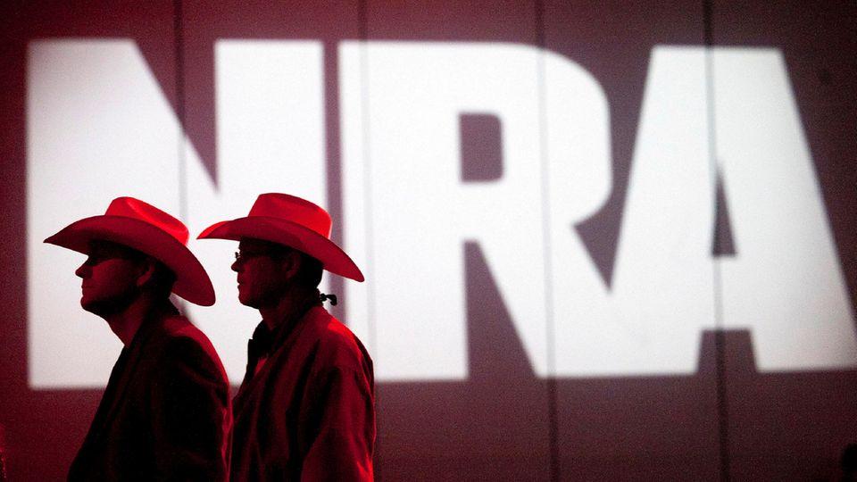 Zwei Personen gehen an einem Schriftzug der NRA vorbei