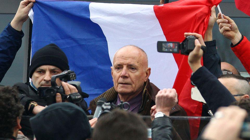 Ein älterer weißer Mann mit sehr kurzen Haaren spricht zu Demonstranten – hinter ihm eine französische Flagge