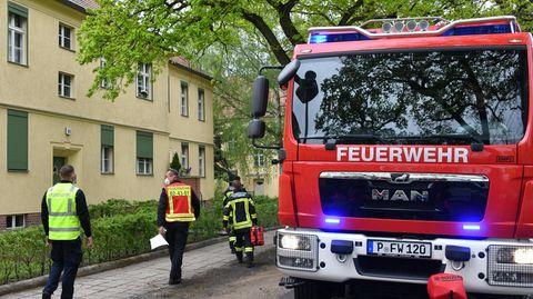 Feuerwehrleute gehen im Sperrgebiet in der Heinrich-Mann-Allee zu einem Haus