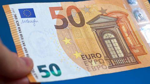 Eine Hand hält einen 50-Euro-Schein.