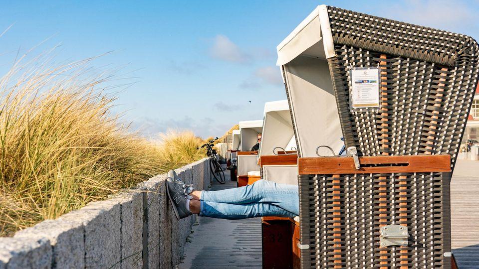 Schleswig-Holstein, Wenningstedt: Eine Frau sitzt auf der Besucherpromenade in einem Strandkorb