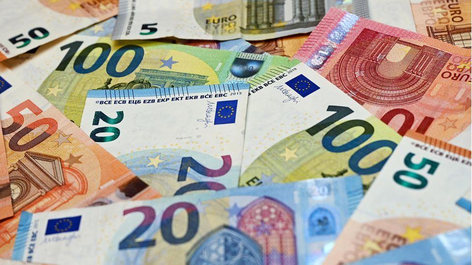 Eurobanknoten liegen auf einem Tisch (gestellte Aufnahme)