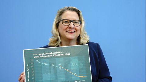Eine Frau mit schulterlangen blonden Haaren hält ein Diagramm auf grünem Hintergrund hoch. Es zeigt die Klimaziele der Regierung