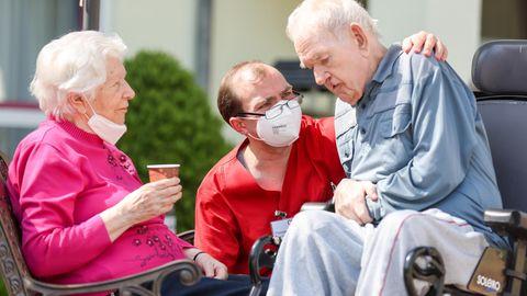 Ein Pfleger kümmert sich um ein altes Paar