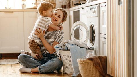 Mutter und Kind sitzen vor der Waschmaschine. Der Sohn drückt seiner Mutter einen Kuss auf die Wange.