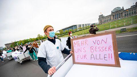 """Ein Teilnehmer der Aktion """"Der Pflege geht die Luft aus"""" geht mit einem Krankenhausbett am Reichstagsgebäude vorbei"""