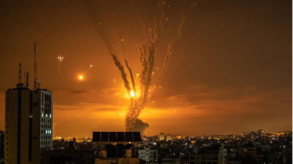 Raketen in Richtung Israel und die israelische Raketenabwehr hinterlassen Streifen am Himmel über Gaza-Stadt