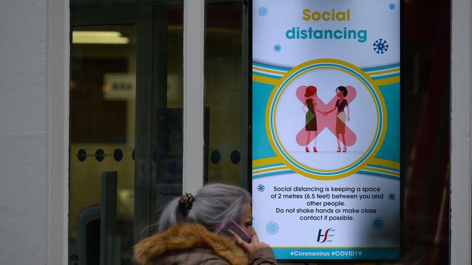 Dublin, Irland: Eine Frau geht an einer Hinweistafel desöffentlichen Gesundheitsdienstes HSE vorbei