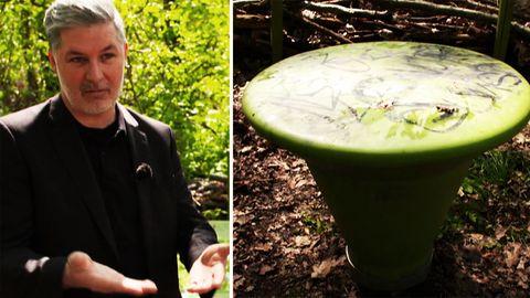 Mann stehet neben grünen Plastikmöbeln in einem Park