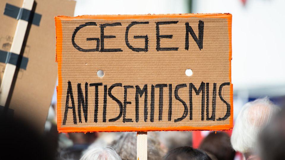 """Ein Person hält bei einer Kundgebung ein Plakat mit der Aufschrift """"Gegen Antisemitismus"""" in die Höhe"""