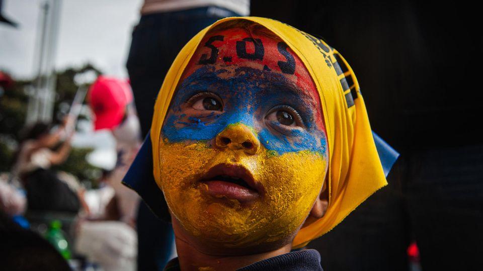 Ein Kind, dessen Gesicht mit den Farben der kolumbianischen Nationalfahne bemalt ist, nimmt an einer Demo teil