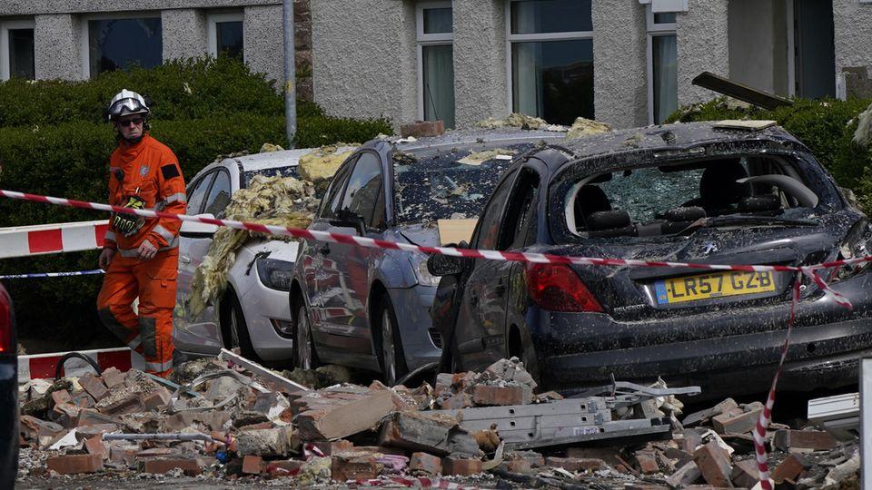 Einsatzkräfte stehen vor einer Reihe zerstörter Autos