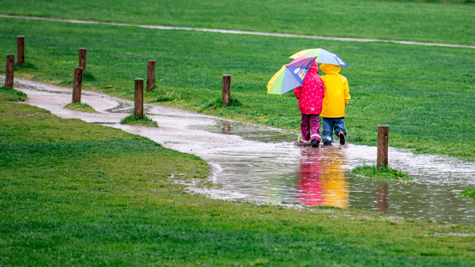 Zwei Kinder spazieren im Regen