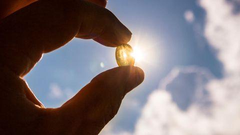 Vitamin D und Corona: eine Frau hält eine Vitamin D-Tablette in der Hand