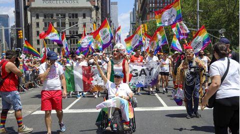 Menschen nehmen an der Pride-Parade in New York teil und schwenken Regenbogen-Flaggen