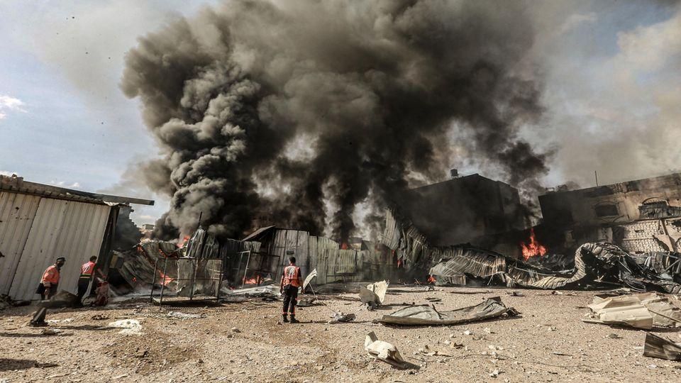 Mitglieder der palästinensischen Zivilverteidigung versuchen, das Feuer in einer Schaumstofffabrik zu löschen