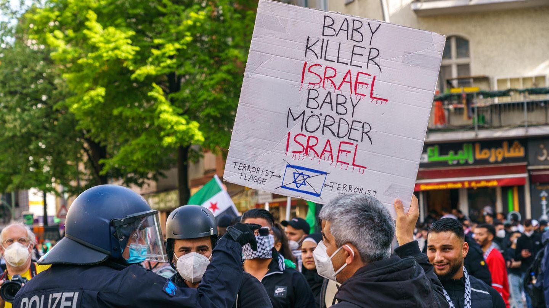 """Demonstranten halten in Berlin ein Schild """"Babymörder Israel"""""""