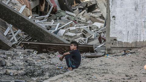 Ein Junge sitzt vor den Trümmern eines eingestürzten Wohnhauses, nachdem es von einem israelischen Luftangriff getroffen wurde