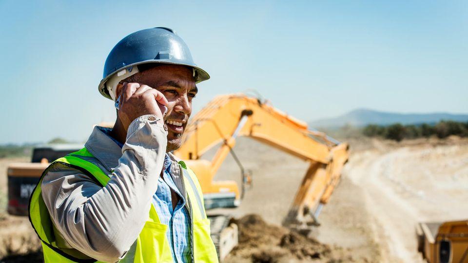 Ein Architekt telefoniert mit seinem Baustellen-Handy.