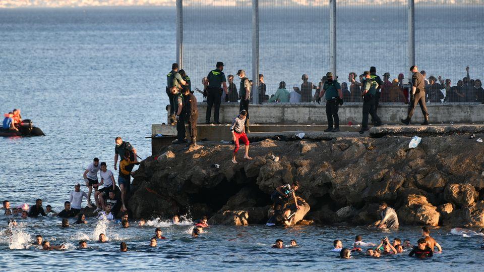 Migranten bei der Ankunft am Ufer der spanischen Nordafrika-Exklave Ceuta