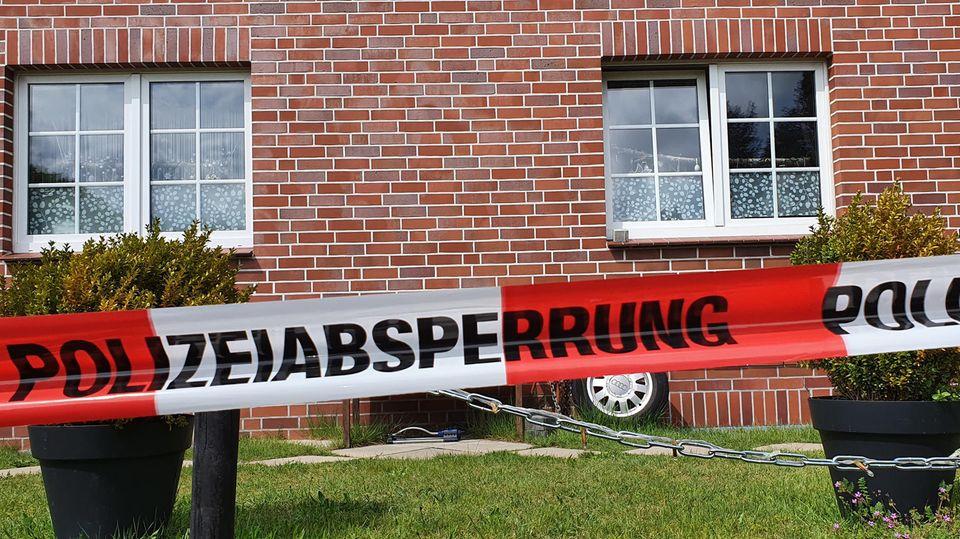 Niedersachsen, Bispingen: Ein Absperrband der Polizei hängt vor einem Haus