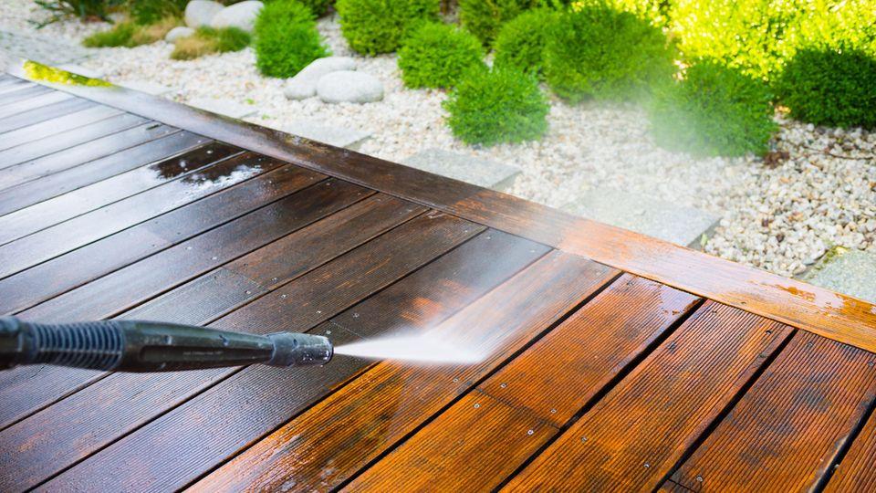 Terrasse reinigen: Wasserstrahl aus einem Hochdruckreiniger trifft auf Holzbohlen einer Terrasse