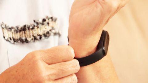 Person legt Fitnesstracker an das Handgelenk an