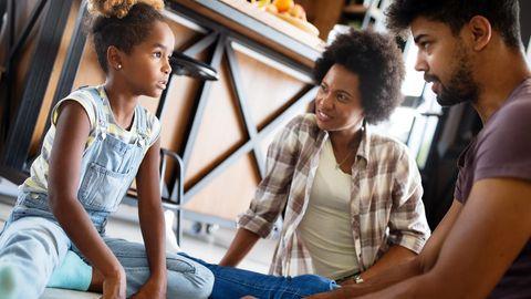 Familie sitzt af dem Boden. Die Eltern erklären der Tochter etwas, die aufmerksam zuhört.