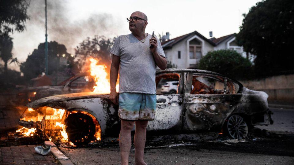 Fassungslos steht Jacob Simona vor seinem brennenden Auto in der israelischen Stadt Lod