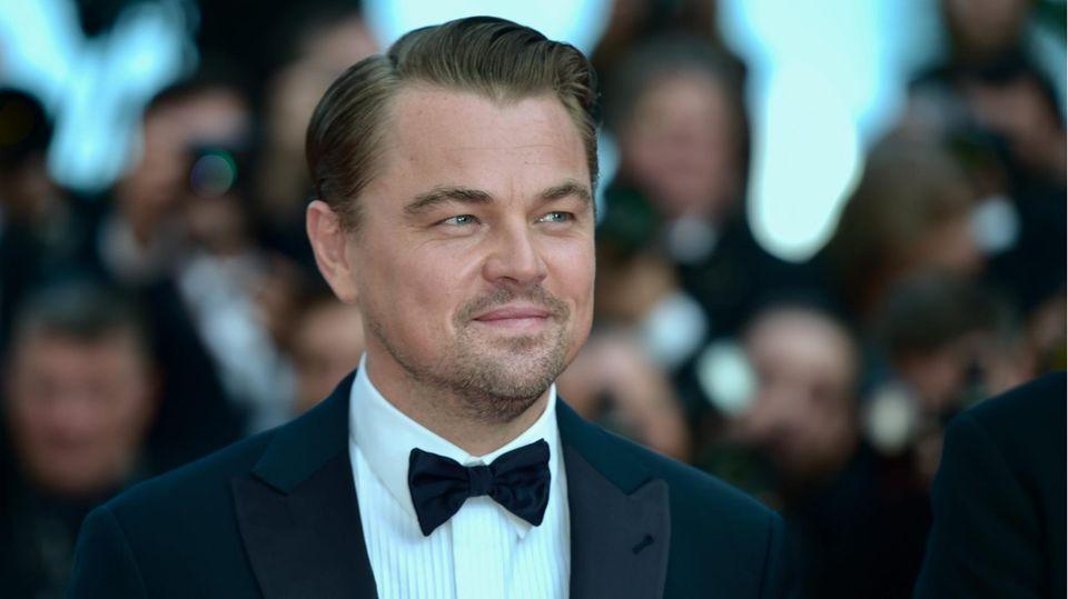 Leonardo DiCaprio auf de roten Teppich mit Fotografen im Hintergrund